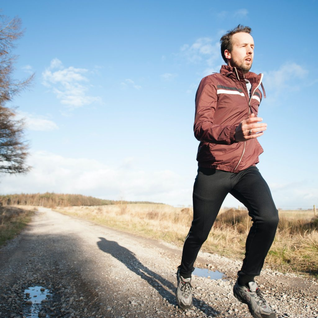 Man running on a gravel road in a windbreaker jacket and tights.