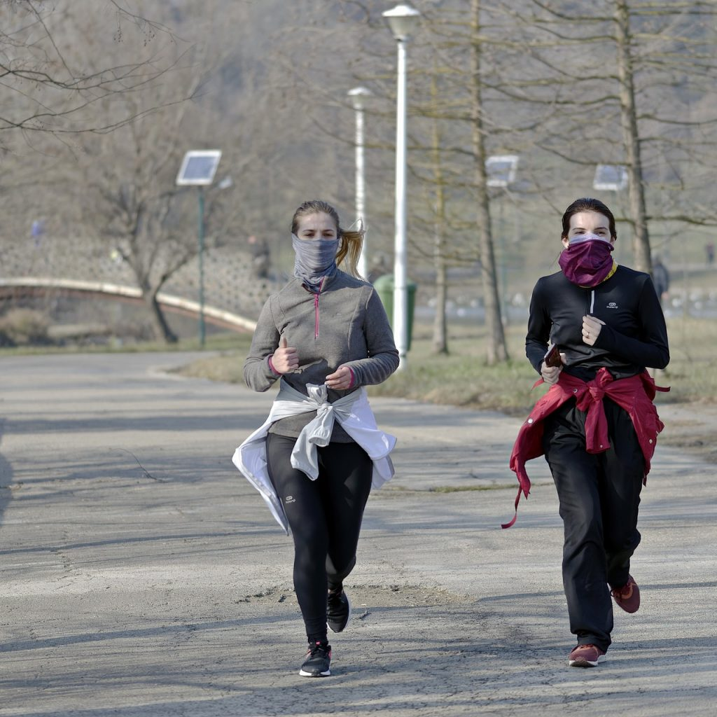Two young women running in cool weather attire with jackets tied around their waists.