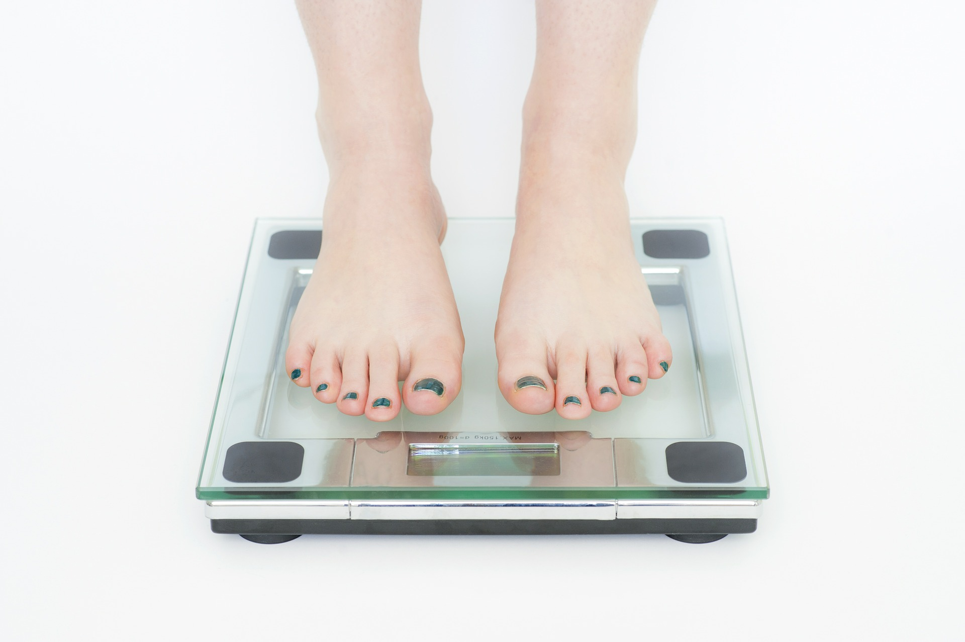 Photo of feet standing on a scale. Scales can show your weight, BMI and body fat.