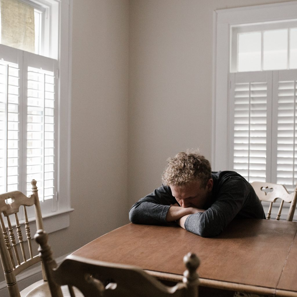 A sad man sits at a table with his head down and his chin on his arms.