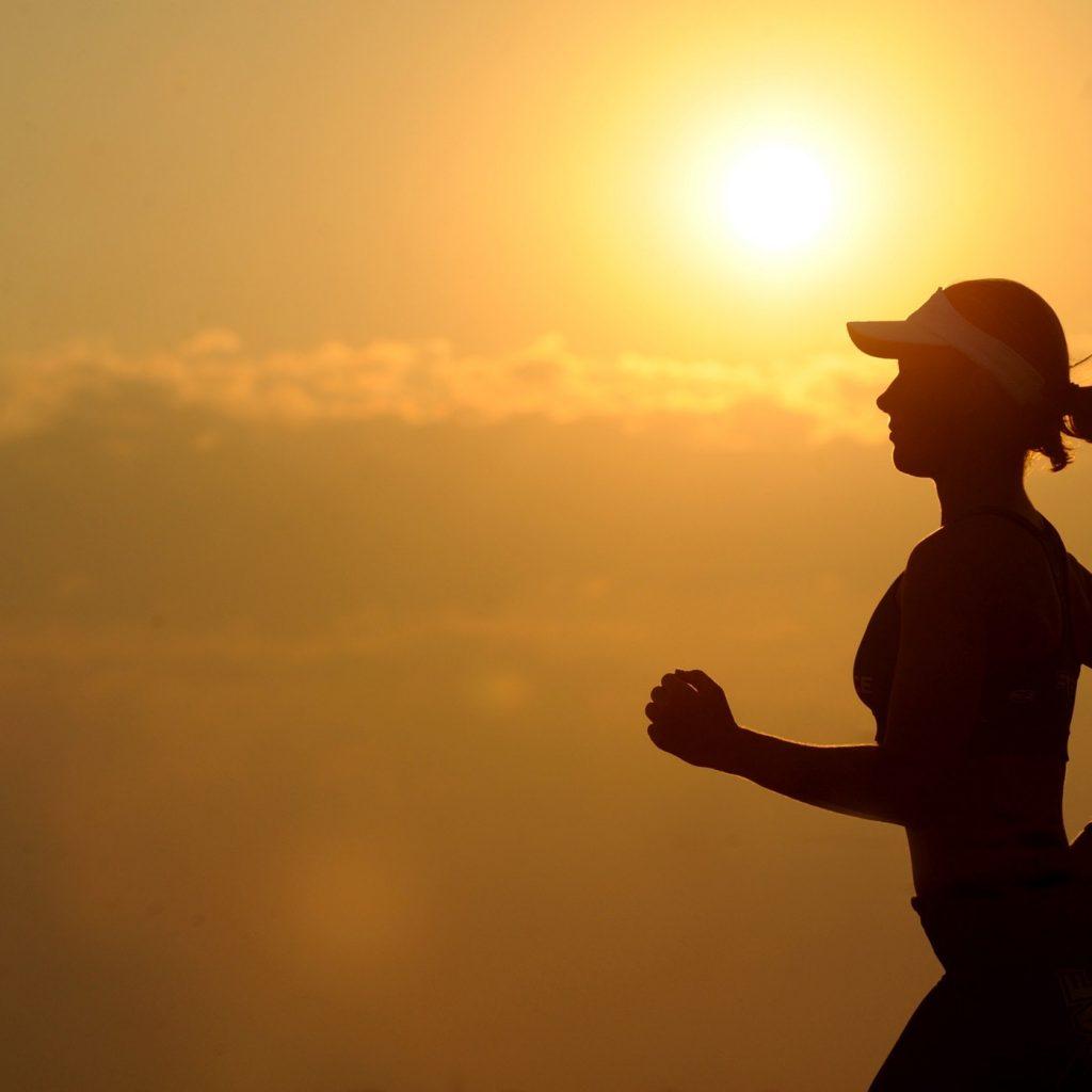 A woman runs while the sun creates a glow.